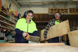 Man and woman working in woodwork workshop